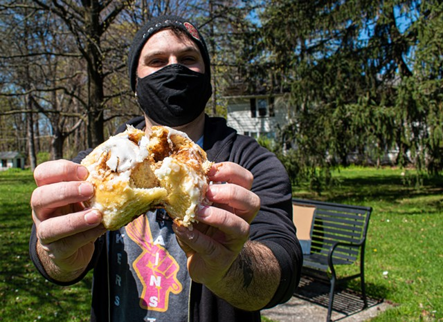 Jon Olek of Black Cat Baking Co., seen here with a cinnamon roll, works from his basement commercial-grade kitchen to supply several area cafes and shops with home-made pastries.