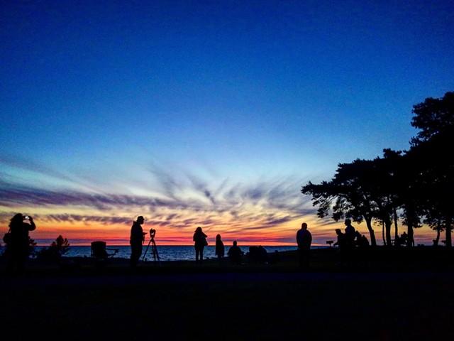 Skywatchers view eclipse from Hamlin Beach.