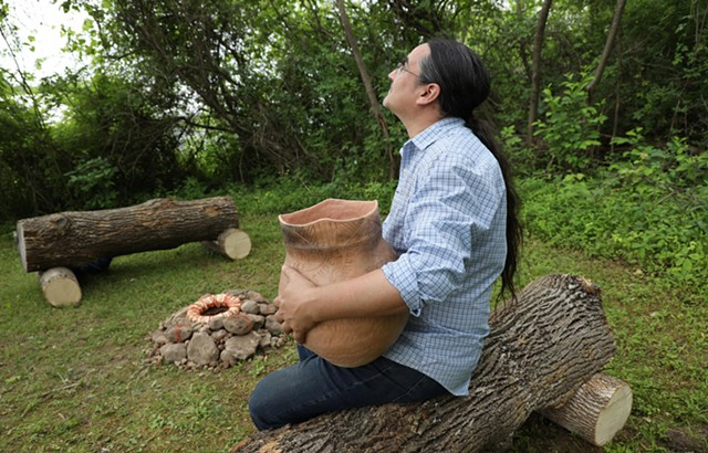 Mike Jones, a Native American artist, holds a clay pot he made for the Earth Altar project. His work, along with other altars, can be seen at the Ganondagan State Historic Site in Victor.
