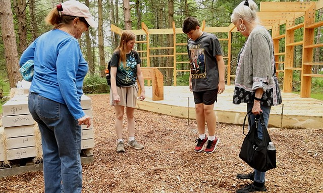 Anne Quivey, Catherine Abida and Pat Strobel watch Ali Abida jump in engineered wood chips that are ADA-compliant and used along the Autism Nature Trail at Letchworth State Park.