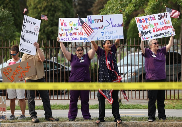 Amanda Coakley, 2nd from right, holds a sign promoting natural immunity at protest against vaccine mandates outside Strong Memorial Hospital