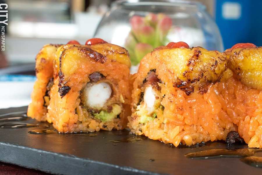 The Merengue Roll features beer-battered shrimp, bacon, Sriracha, and avocado, and is topped with sweet plátanos and Stingray Sauce. - PHOTO BY JACOB WALSH