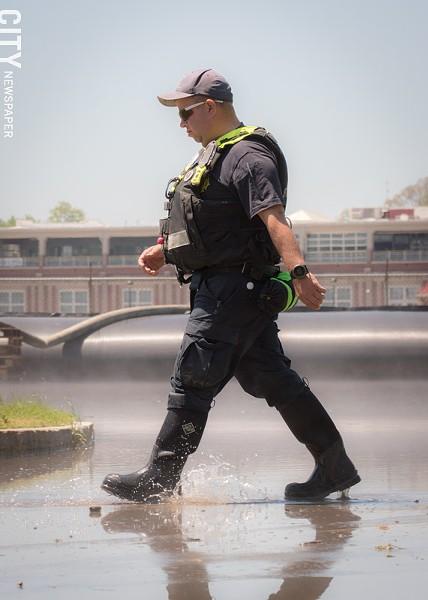 An emergency worker walks through flood waters. - PHOTO BY RYAN WILLIAMSON