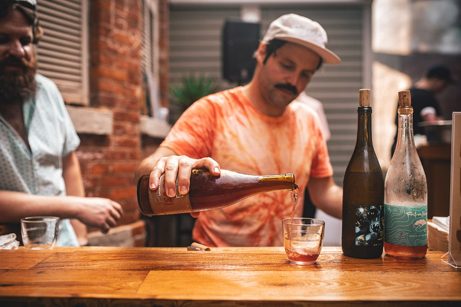 Brandon Opalich pours curated wine selections at the first Aldaskeller Wine Co. pop-up tasting event at Swan Dive. - PHOTO BY JASON CAMPBELL