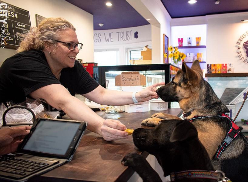 Bones Bakery owner Dani Lawson treats Cooper and Penny to pooch-friendly pumpkin muffins. - PHOTO BY JACOB WALSH