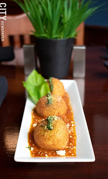For starters: the four cheese arancini topped with tomato sauce and pesto. - PHOTO BY JACOB WALSH