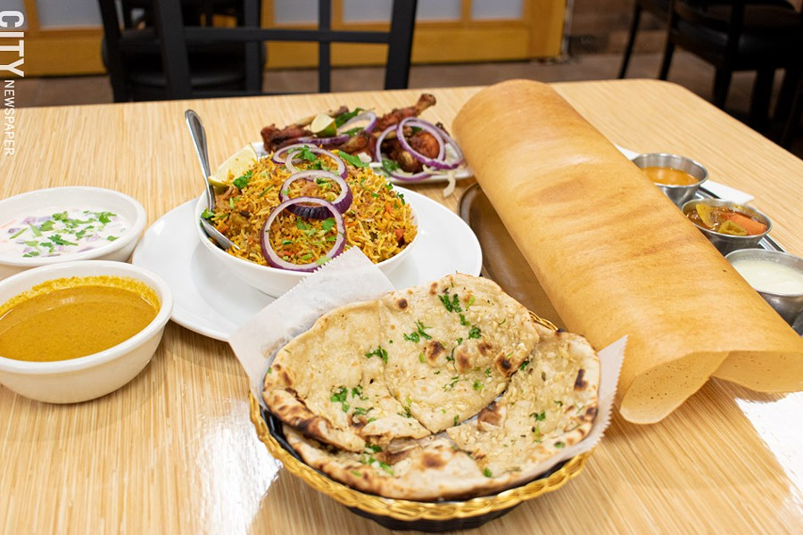 Clockwise from front: garlic naan, vegetable biryani with yogurt raitha and sarlan (chili pepper and peanut gravy), chicken lollipops, and dosa with chutneys (coconut, sambhar, and tomato). - PHOTO BY JACOB WALSH