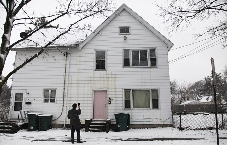 Mike Furlano, an attorney with the Legal Aid Society of Rochester, photographs the damaged exterior of 445 Sherman Street. - PHOTO BY MAX SCHULTE