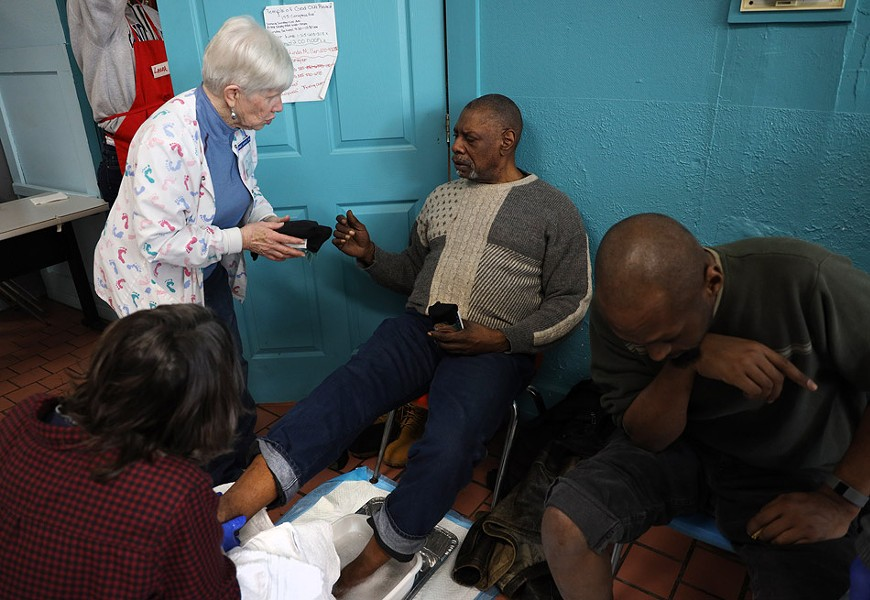 Debbie Sigrist, the founder of the St. Joseph's House of Hospitality foot clinic, offers a guest a new pair of socks. - PHOTO BY MAX SCHULTE