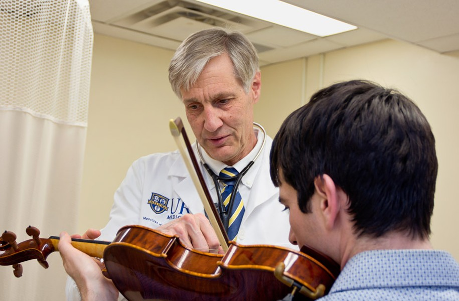 Dr. Ralph Manchester of Eastman Performing Arts Medicine works with a violinist. - PHOTO COURTESY OF THE UNIVERSITY OF ROCHESTER MEDICAL CENTER