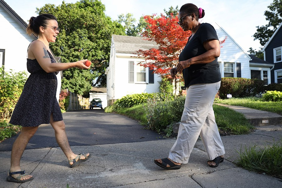 Lindsey Downey brings a peach to her neighbor, Janet Williams. - PHOTO BY MAX SCHULTE