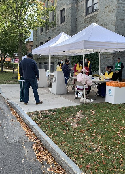 Staff register people for free COVID-19 testing and flu vaccinations at Aenon Baptist Church on Genesee Street. - CREDIT WXXI NEWS