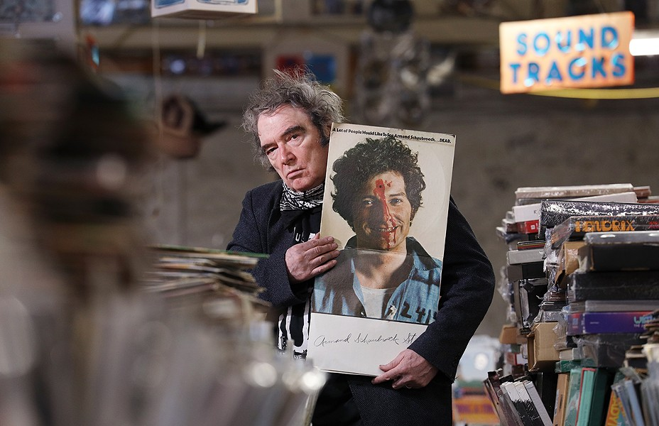 "Armand Schaubroeck, co-owner of the House of Guitars and a former rock artist, displays the album he cut in 1968, ""A Lot of People Would Like to See Armand Schaubroeck . . . DEAD."" - PHOTO BY MAX SCHULTE"