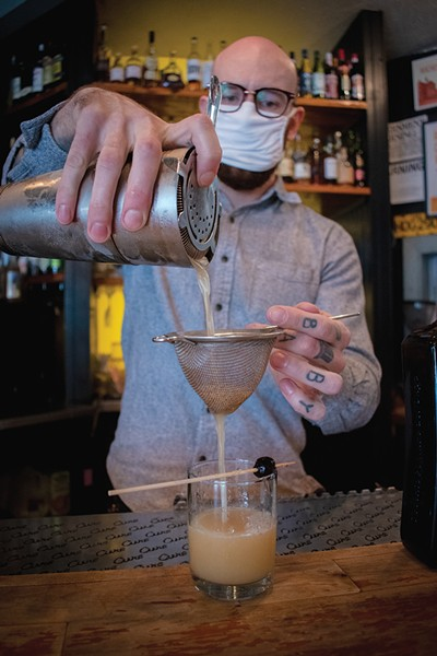 """Cure's head bartender Donny Clutterbuck mixing up """"Fashionably Late,"""" which blends the flavors of orange, clove, molasses, and lemon juice. - PHOTO BY RYAN WILLIAMSON"""