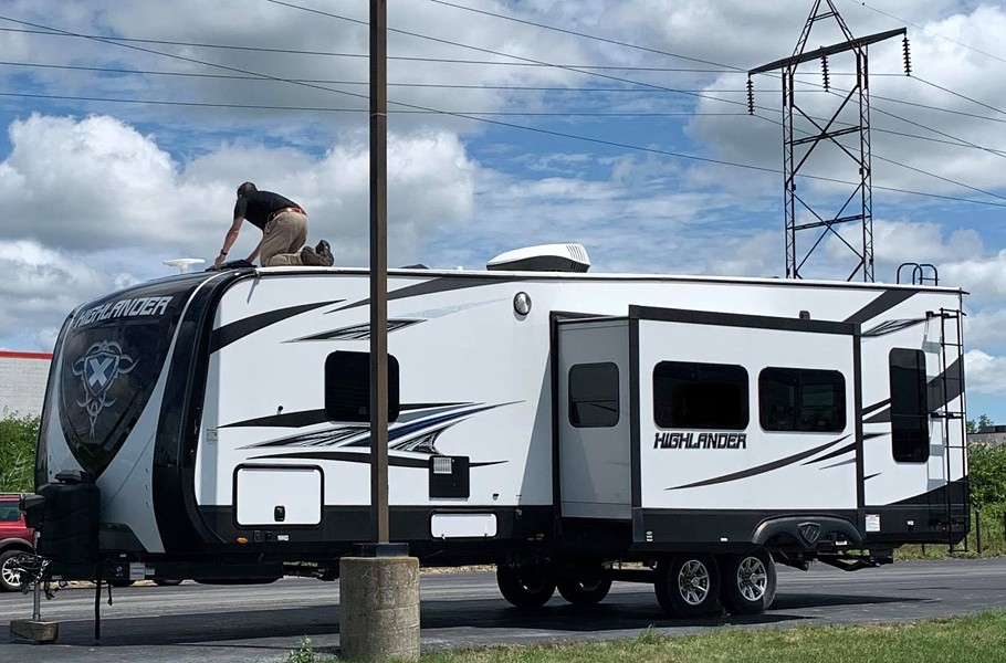 Tim Clark works on the roof of the RV. - PHOTO PROVIDED BY COLLINS AND CLARK