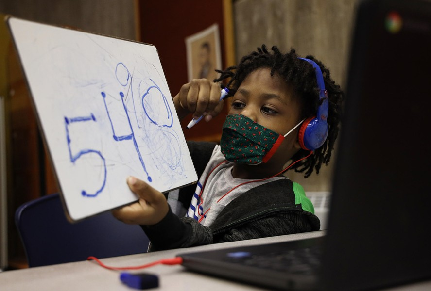 Kaleb Wilcoxson, a kindergartner, shows his work to his virtual class on a whiteboard. - PHOTO BY MAX SCHULTE / WXXI NEWS