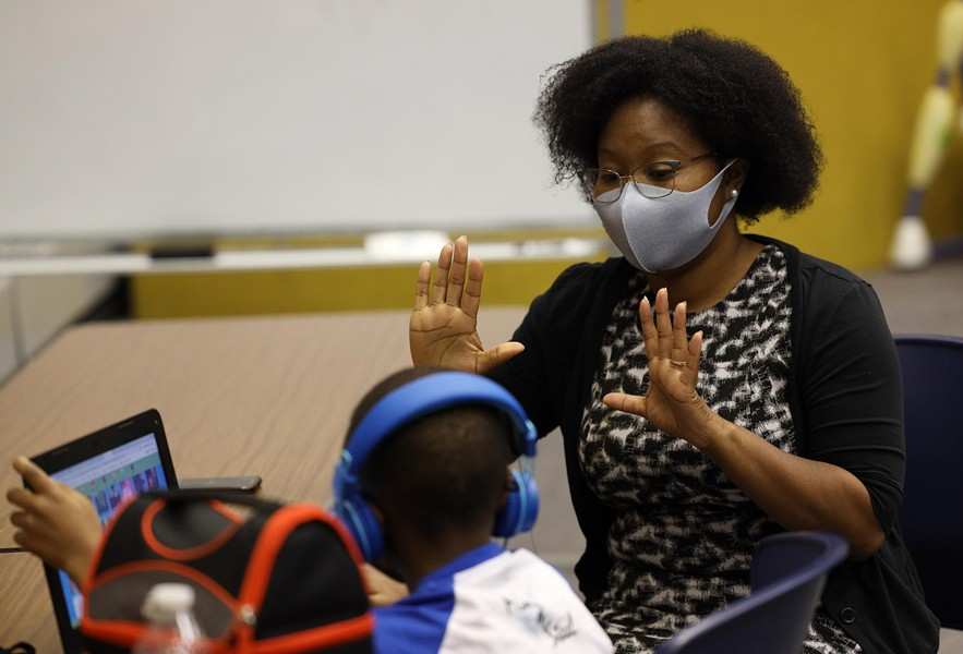 Brittany Rumph gives first-grader T'Aires Cheek a visual reminder that his next virtual class begins in 10 minutes. - PHOTO BY MAX SCHULTE / WXXI NEWS