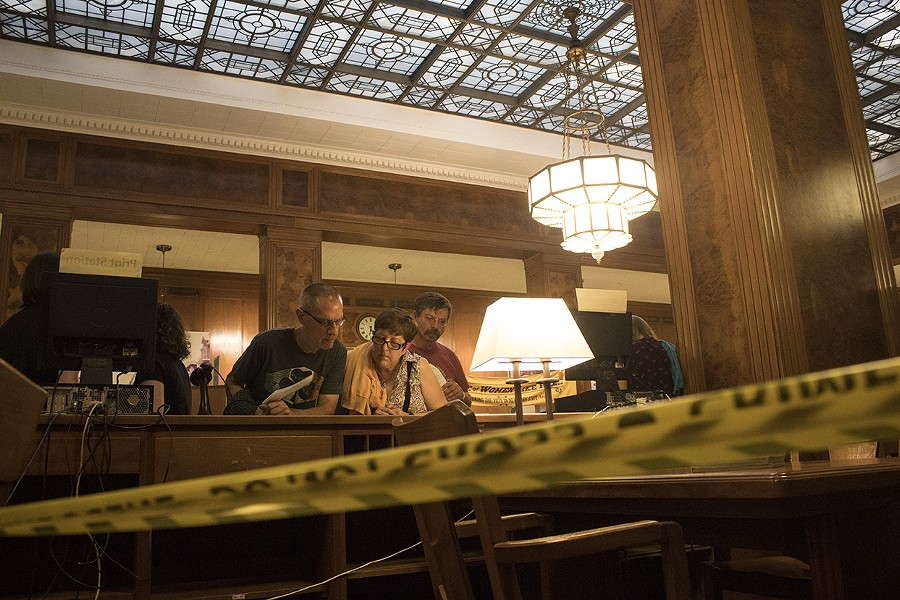 People examine clues during the Murder Mystery at the Central Library. - PHOTO BY ASHLEIGH DESKINS