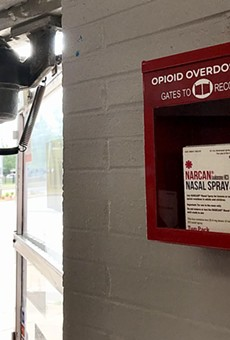 An emergency Narcan box is positioned next to the front door of Boost Mobile at 570 W. Main St.