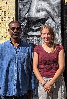Artists Richmond Futch Jr. and Chloe Smith in front of the completed book spine mural at Arnett Branch Library.