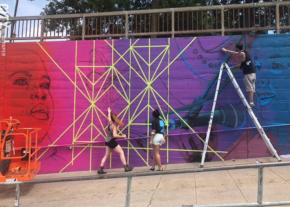 """Artist Sarah Rutherford and youth apprentice Tehya Bollar tape off geometric lines while artist Justin Suarez (aka Mr. Prvrt) applies paint to """"This is Triumphant Music,"""" the Wall\Therapy mural featuring Rochester musicians at Martin Luther King Jr. Park. - PHOTO BY REBECCA RAFFERTY"""