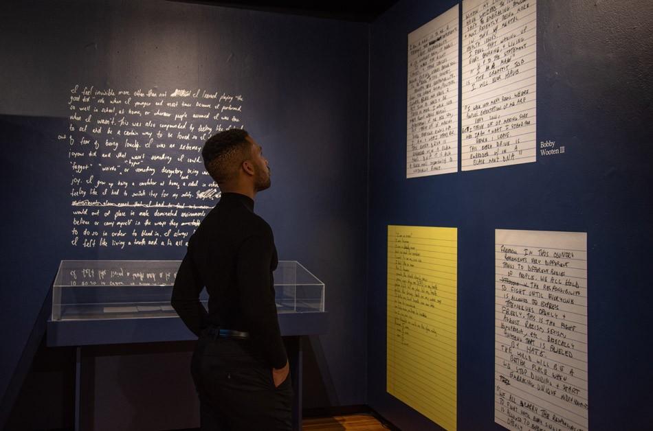 "Artist Joshua Rashaad McFadden with his installation, ""Evidence,"" at Visual Studies Workshop. - PHOTO BY SARI OISTER"