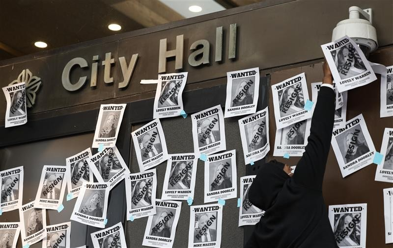 During a protest at City Hall Tuesday, demonstrators hung flyers demanding that Mayor Lovely Warren and District Attorney Sandra Doorley resign. - PHOTO BY MAX SCHULTE