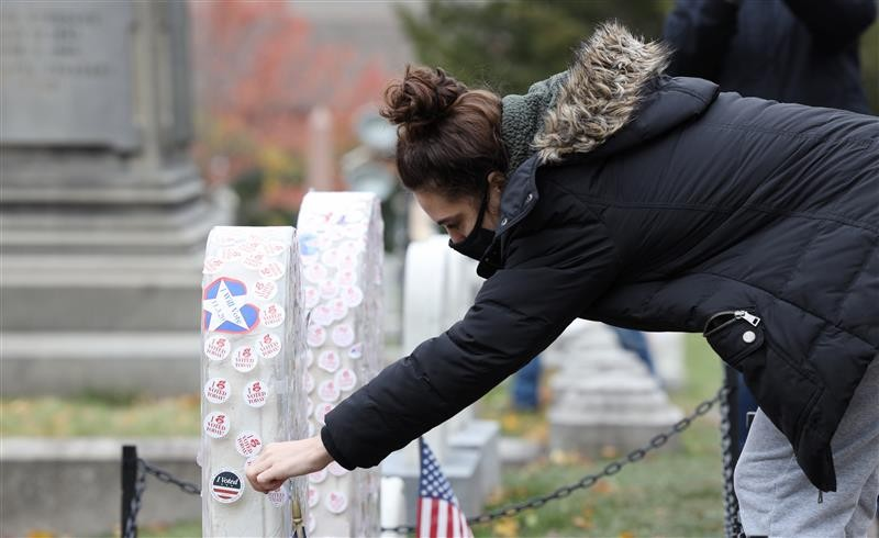 "Abby Richards, 20, of Victor, places her ""I Voted sticker on Susan B. Anthony's grave. - PHOTO BY MAX SCHULTE"