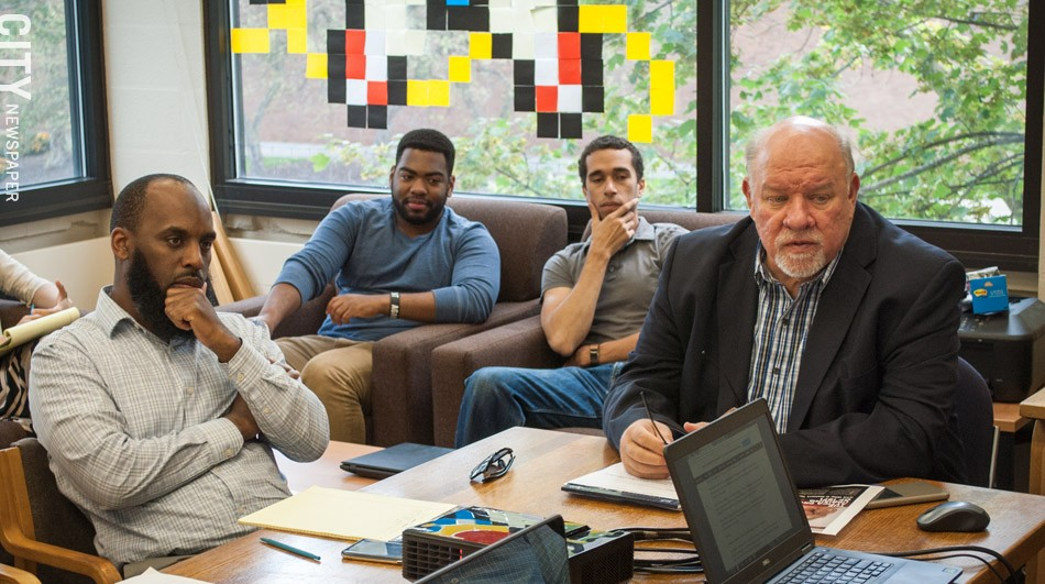 John Klofas (right), director of the Center for Public Safety Initiatives at RIT, with (from left) Irshad Altheimer, the center's deputy director, and research assistants Chaquan Smith and Aaron Baxter, at the center's weekly research meeting. - PHOTO BY RYAN WILLIAMSON