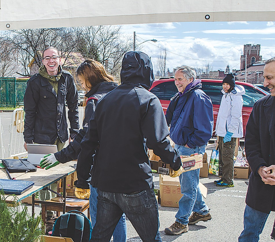 FCP Acting Director Evan Zachary (left) with volunteers at the Public Market. - PHOTO COURTESY FLOWER CITY PICKERS