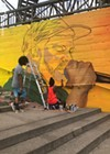 Youth apprentice Alex Baez Rivera looks on as artist Brittany Williams works on a section of the mural featuring Moses Rockwell.