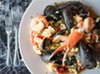 The Poseidon includes shrimp, scallops, lobster, crab, calamari, and mussels sautéed with sun dried tomatoes, roasted red peppers, and artichoke hearts in a lemon garlic sauce, over a bed of Spanish rice.