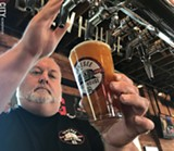 PHOTO BY RYAN WILLIAMSON - Dean Jones pours a beer at the Genesee Brew House. Jones is a member of the 585 Brewers Collaborative, a group of 10 local breweries that recently - released a popular India Pale Lager.