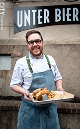 PHOTO BY RYAN WILLIAMSON - Unter Biergarten Chef and owner Derrick DePorter holds the Knackwurst.