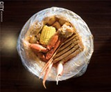 PHOTO BY JACOB WALSH - Bagged goods: Crab legs, salt potatoes, and sweet corn on the cob at Juicy Seafood.