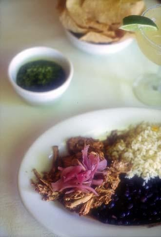 A plate of Cochinita Pibil with rice and beans, and the astounding green salsa nearby.