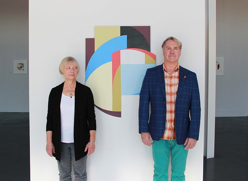 Artists Constance Lowe and Gary Sweeney stand stiffly in front of one of Lowe's geometric abstractions. - COURTESY