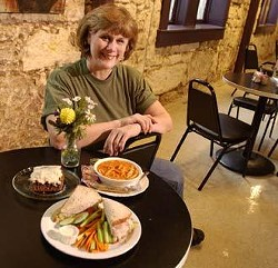 Connie Marshall, owner and visionary behind Leap of Faith CafÈ, sits with samples of her fare. Clockwise from front: Baby Boomer sandwich - turkey, avocado, mayonnaise, and sprouts on whole wheat bread; Hummingbird cake - carrot cake with bananas and pineapple and cream cheese frosting; a bowl of tomato pasta soup.