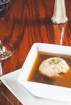 A single dumpling floats atop an honest bouillon soup