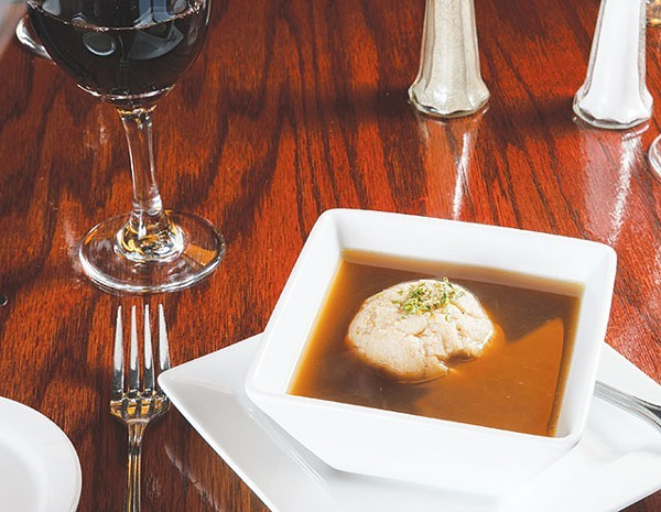 A single dumpling floats atop an honest bouillon soup - WWW.PAYTONPHOTOGRAPHY.COM