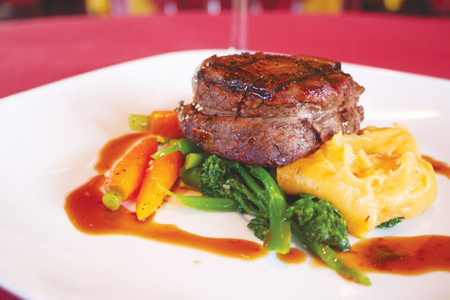 Filet mignon on a bed of vegetables from McCullough Avenue Grill. - VERONICA LUNA
