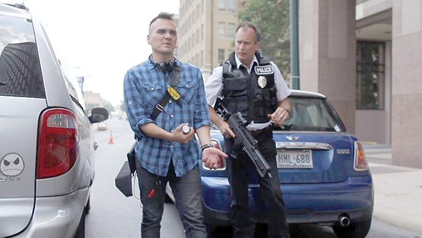 Filmmaker Mark Cantu (left) demonstrates the correct way to unload an assault rifle to actor James Allen Chapman in downtown SA - COURTESY PHOTO