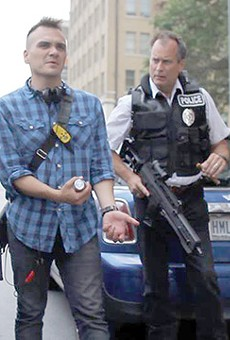 Filmmaker Mark Cantu (left) demonstrates the correct way to unload an assault rifle to actor James Allen Chapman in downtown SA
