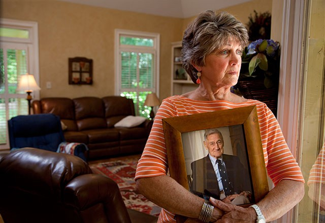 George McAfee's daughter holds a photo of her father, who died after swallowing toxic dishwashing liquid at an Emeritus facility in Georgia - COURTESY PHOTO
