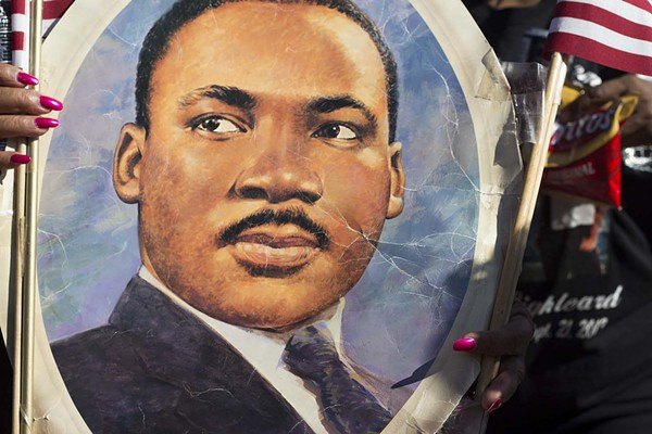 A participant in the 2014 MLK Day March in San Antonio holds up an image of Dr. Martin Luther King, Jr. - RICK CANFIELD