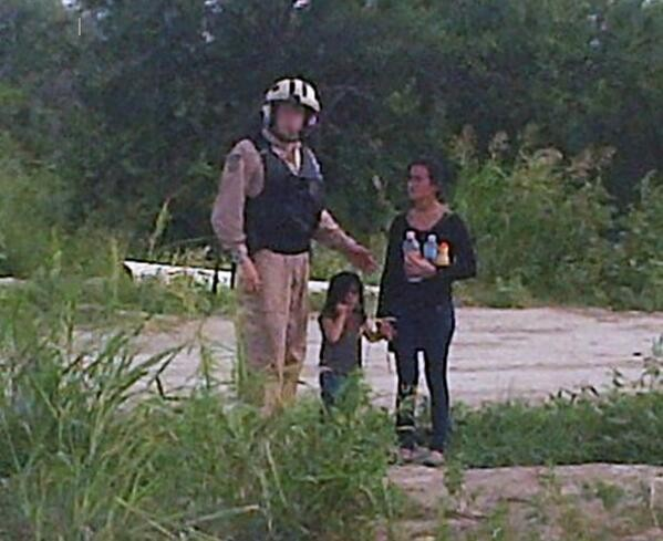 In this photo taken by Border Patrol in the Rio Grande Valley earlier this year, a teenage girl and young child are rescued by authorities after becoming lost and dehydrated. They were most likely turned over to Immigration and Customs Enforcement. - U.S. BORDER PATROL