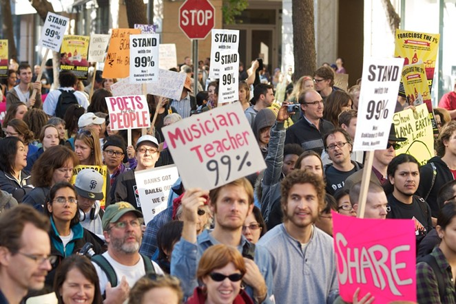 "Protestors carry ""We are the 99 percent"" signs during an Occupy protest in 2011. - WIKIMEDIA COMMONS"