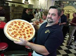 Steve Florio shows off a freshly made New Jersey-style pepperoni pizza at his family's Linclon Heights eatery.