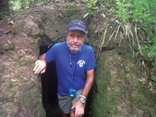 The author climbing out of a cramped secret bunker used by the Viet Cong in South Vietnam.