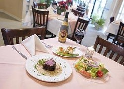 """The chef's own """"""""sensation"""""""" beef tenderloin - pan seared with peppercorns and served with an onion, cream, and cognac sauce, accompanied by sautéed cauliflower and asparagus. It is shown here with a house salad, and a bottle of Faustino Primero."""